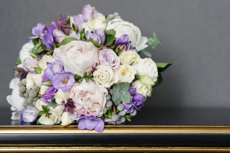 Brudar som gifta sig buketten med pioner, freesia och andra blommor på den svarta tabellen Ljus och lila vårfärg Morgon in arkivbilder