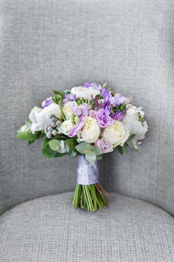 Brudar som gifta sig buketten med pioner, freesia och andra blommor på svart armstol Ljus och lila vårfärg Morgon arkivfoto
