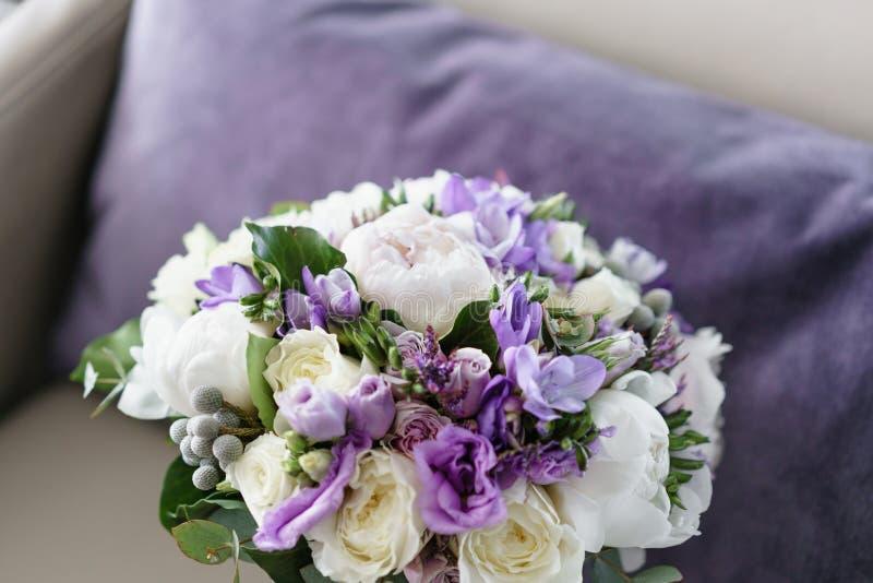 Brudar som gifta sig buketten med pioner, freesia och andra blommor på svart armstol Ljus och lila vårfärg Morgon arkivbilder