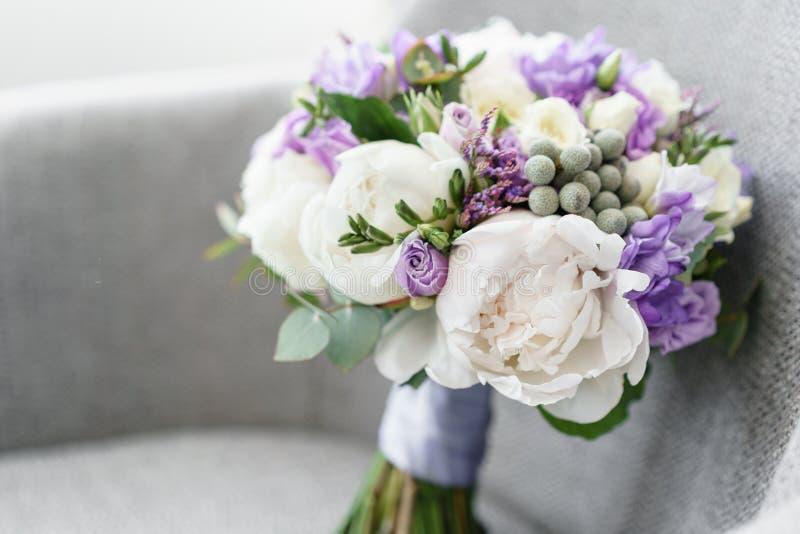 Brudar som gifta sig buketten med pioner, freesia och andra blommor på svart armstol Ljus och lila vårfärg Morgon royaltyfria foton