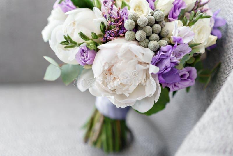 Brudar som gifta sig buketten med pioner, freesia och andra blommor på svart armstol Ljus och lila vårfärg Morgon fotografering för bildbyråer