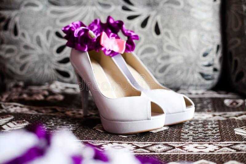 Brudbröllop skor den vita och purpurfärgade strumpebandet arkivfoto