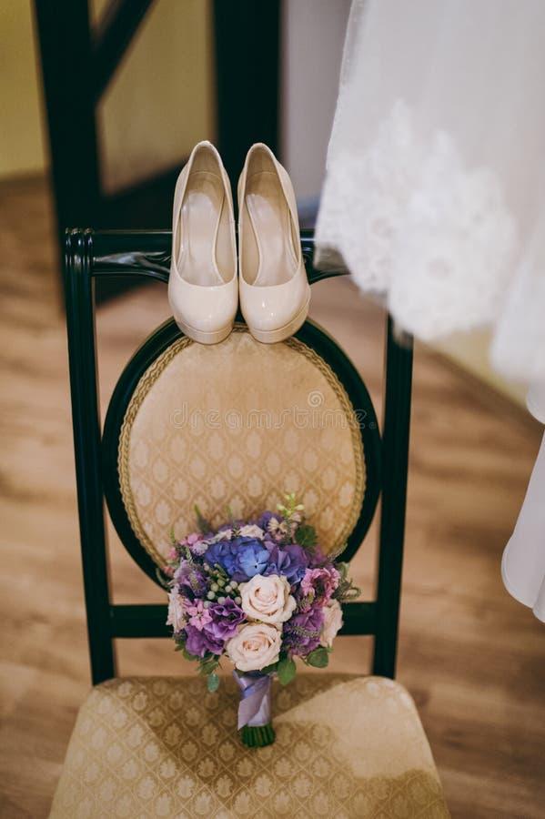 Brudbröllopskor med höga häl och briljanta örhängen för silver på kläder för får` s royaltyfri foto