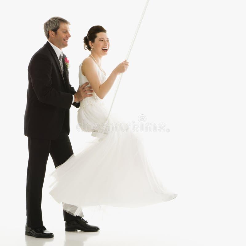brudbrudgum som skjuter swing royaltyfri foto