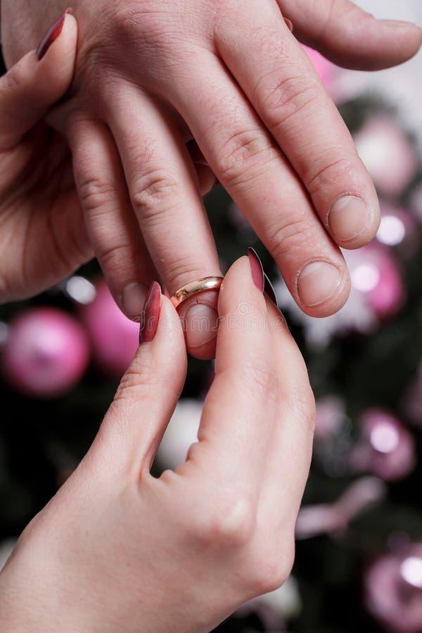Bruden bär cirkeln till brudgummens finger på bröllopdagen Förälskelse som är lycklig att gifta sig begrepp Julfilial och klockor arkivbild