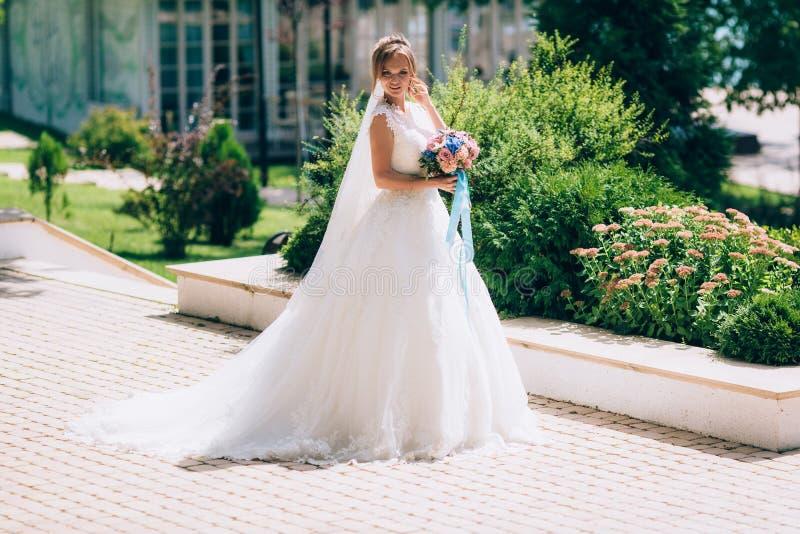 Bruden bär en curvy klänning och går med ett långt skyler längs den pittoreska avenyn Att gifta sig går med en bukett fotografering för bildbyråer