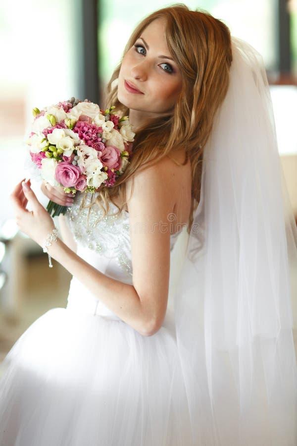 Bruden blandar hennes hår och rymmer bröllopbuketten i henne armar arkivfoto