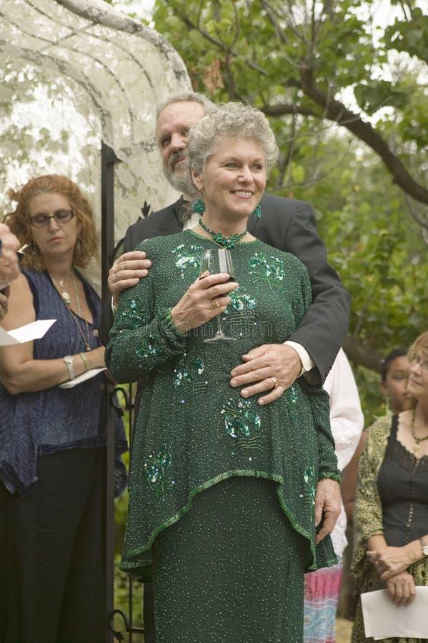 Bruden, brudgummen och gäster delar vin på ett traditionellt judiskt bröllop i Ojai, CA royaltyfri fotografi