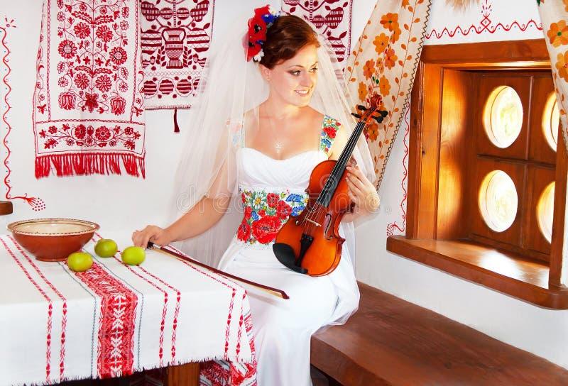 Bruden i den ukrainska stilen rymmer fiolen royaltyfri bild
