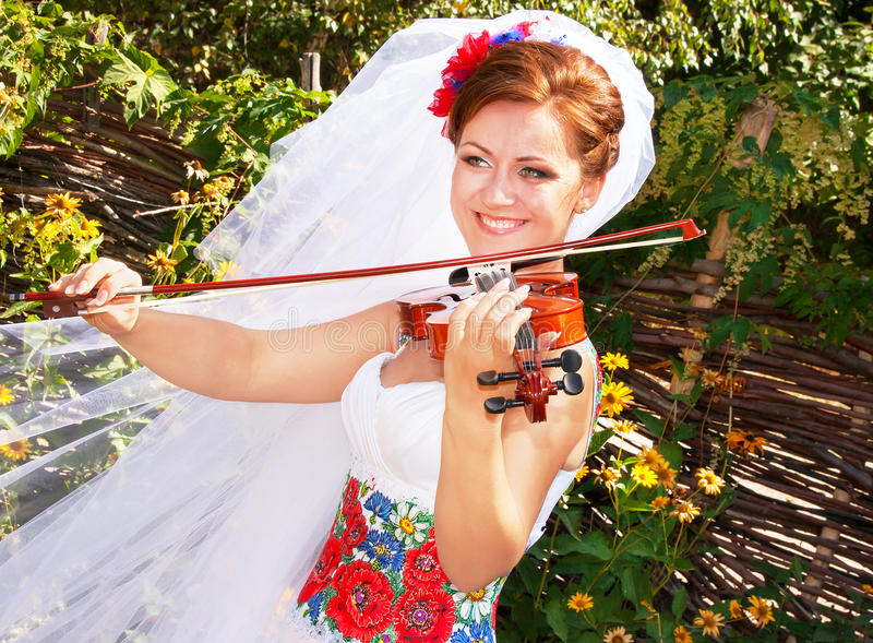 Bruden i den ukrainska stilen spelar fiolen arkivfoton