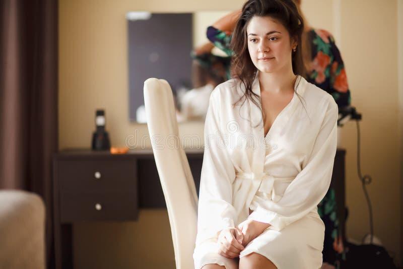 Bruden i den vita badrocken med hennes hår som göras på morgonen Bröllopsklänning och skor arkivfoton