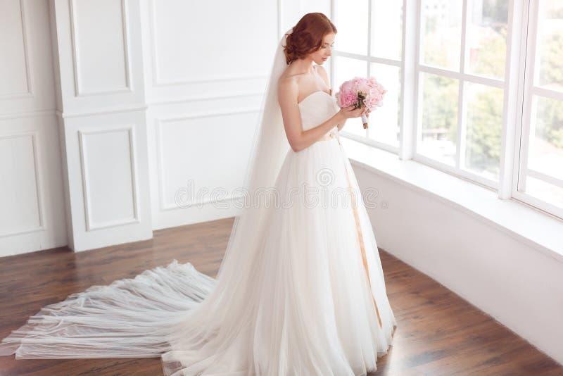 Bruden i den vita bröllopsklänningen och skyler länge med buketten av blommor arkivbild