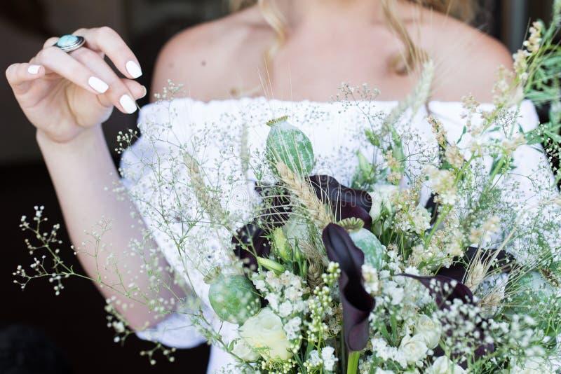 Bruden i den vita bröllopsklänningen rymmer en bröllopbukett med vallmo utomhus- royaltyfria foton