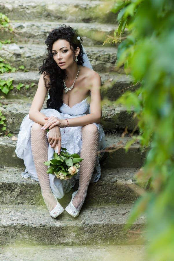 Bruden i den vita klänningen med buketten sitter på trappa royaltyfria foton