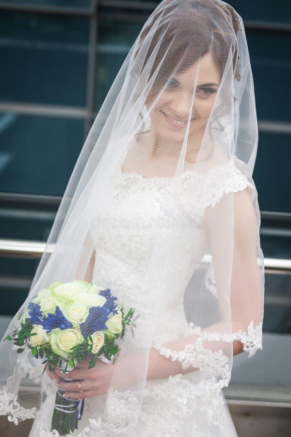 Bruden i den vita klänningen och skyler mot av stadsarkitekturen arkivfoton