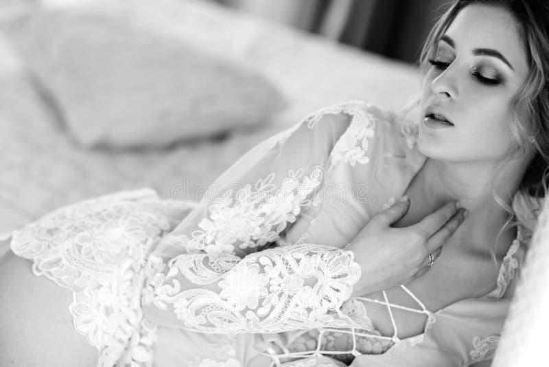 Bruden i en badrock till sovrumfönstret i morgonen royaltyfri bild