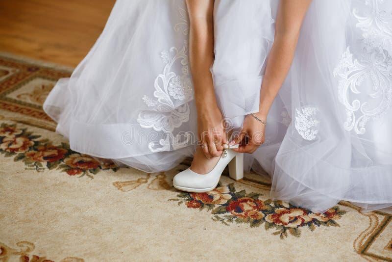 Bruden i en härlig bröllopsklänning sätter på skor, brudens morgonsammankomsterna royaltyfri foto