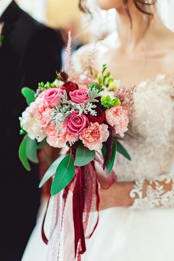 Bruden i en lyxig bröllopsklänning med snör åt att rymma en bröllopbukett gjord av rosor arkivfoton