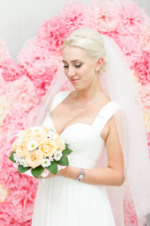 Bruden i en vit klänning och bukett fotografering för bildbyråer