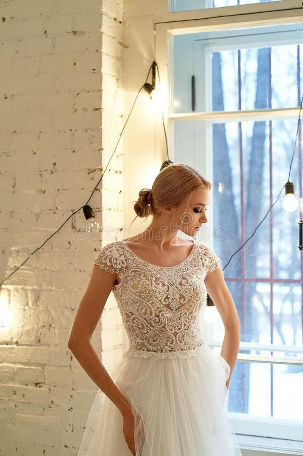 Bruden i en vit sn?r ?t kl?nningen med den broderade kl?nningslivet, inomhus i vindstil H?g tangent royaltyfria bilder