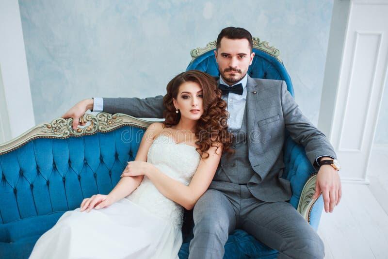 Bruden i härlig klänning och brudgummen i grå färger passar sammanträde på soffan inomhus i den vita studioinre som hemma royaltyfria foton