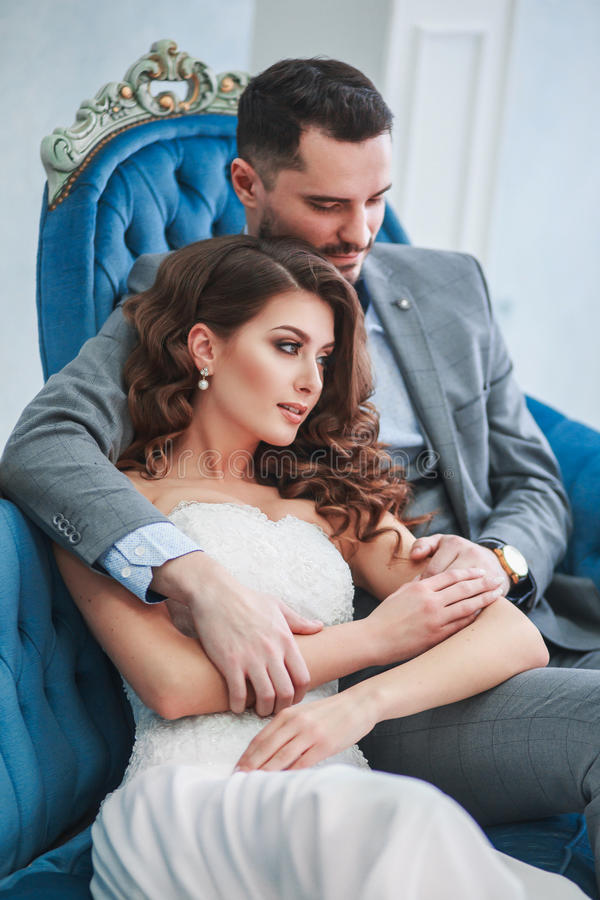 Bruden i härlig klänning och brudgummen i grå färger passar sammanträde på soffan inomhus i den vita studioinre som hemma arkivbilder