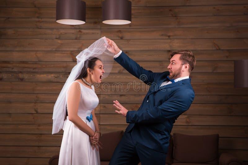 Bruden i klänning och skyler mot brudgum i dräkt royaltyfri foto