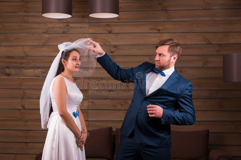 Bruden i klänning och skyler mot brudgum i dräkt royaltyfri bild