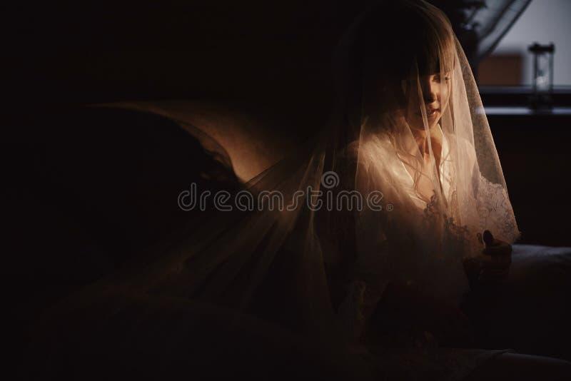 Bruden i sexig underkläder eller nattklänningen från skyler på hennes huvud sitter i rummet på fåtöljen hemma royaltyfri foto
