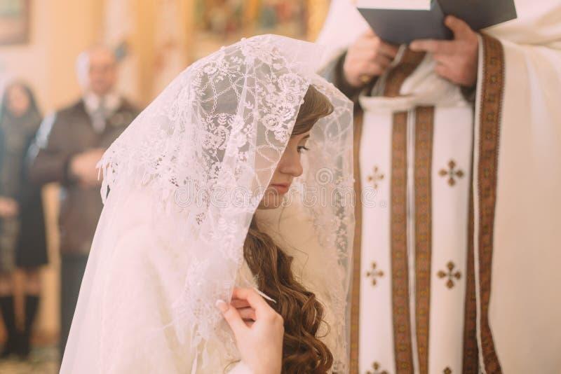 Bruden i vit skyler på kyrkan under en bröllopceremoni arkivbild