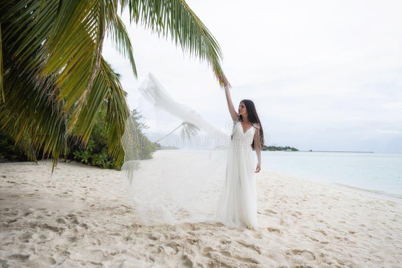 Bruden kastar en vit klänning i luften royaltyfri foto