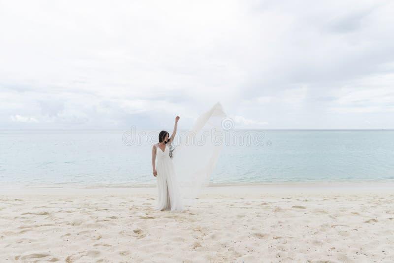 Bruden kastar en vit klänning i luften arkivfoto