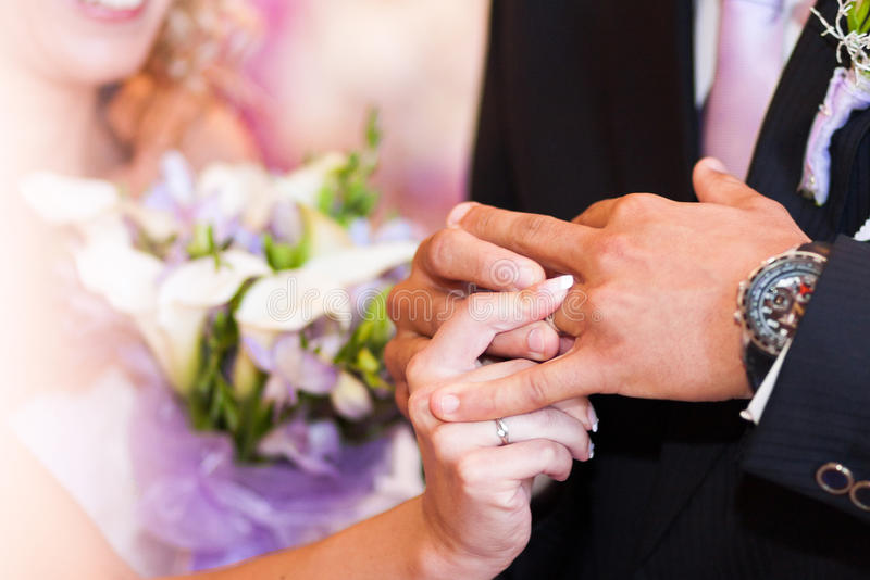 Bruden klär en vigselring till brudgummen arkivfoton