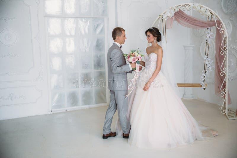 Bruden kramar brudgummen och rymmer en bukett av blommor i hennes händer Ett härligt par av nygifta personer på en bröllopdag royaltyfri foto