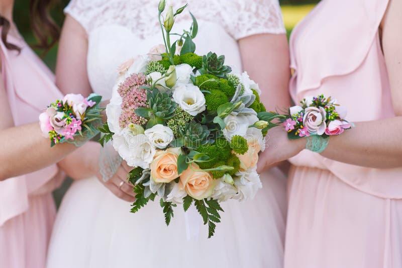 Bruden med brudtärnor rymmer bröllopbuketter arkivfoto