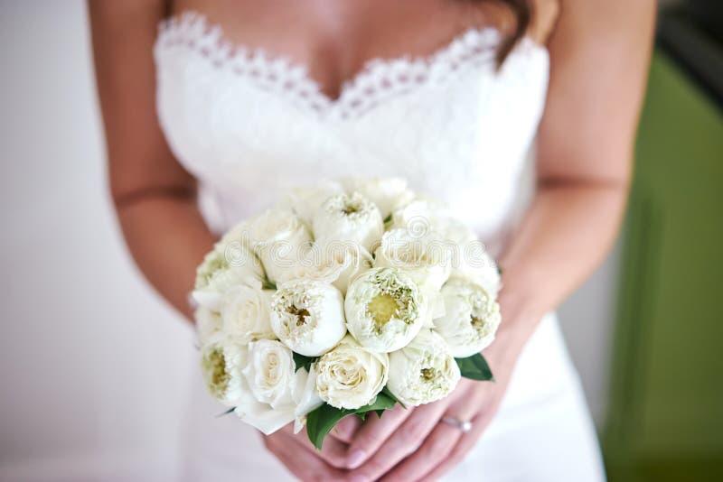 Bruden med buketten som göras med vitkrämlotusblomma och rosor, blommar, fokuserar på buketten - som stängs upp arkivfoto