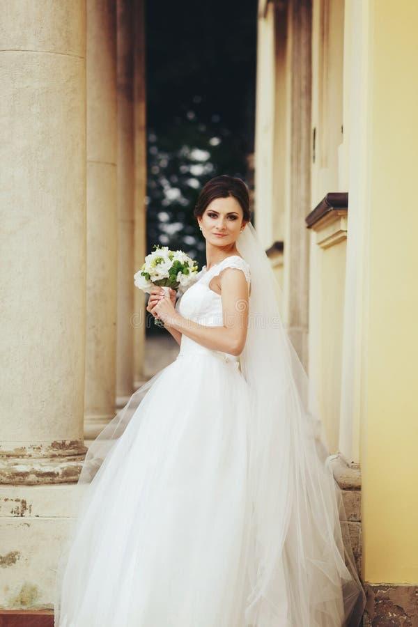 Bruden med en bröllopbukett i hennes armar poserar i passagen är royaltyfri fotografi