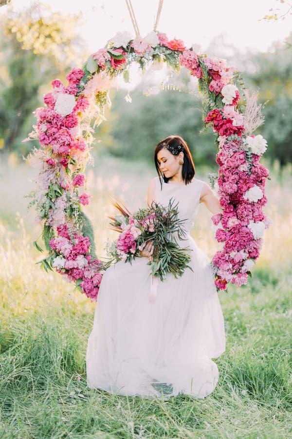 Bruden med hårtillbehören som rymmer buketten av pioner, ser jordningen och sitter i bröllopet royaltyfri foto
