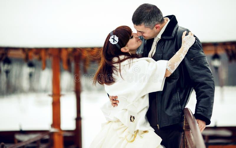 Bruden når ut för en brudgums kyss, medan han kramar henne på wina arkivbild