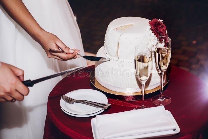 Bruden och bröllopstårtan och avsmakning för brudgum den bitande på bröllop cere royaltyfria bilder