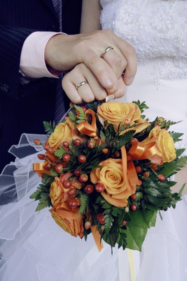 Bruden och brudguminnehav räcker royaltyfri foto