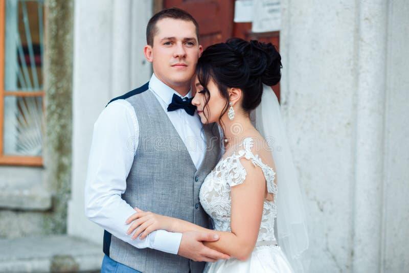 Bruden och brudgummen att krama sig arkivfoto