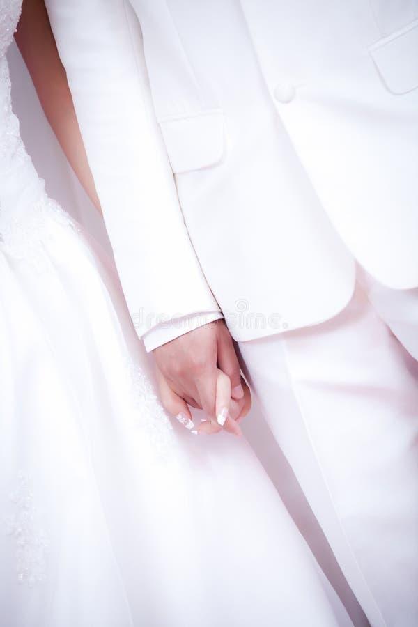 Bruden och brudgummen bär vita klänning- och för vitdräktinnehavet händer på ceremoni för bröllopdag arkivfoton