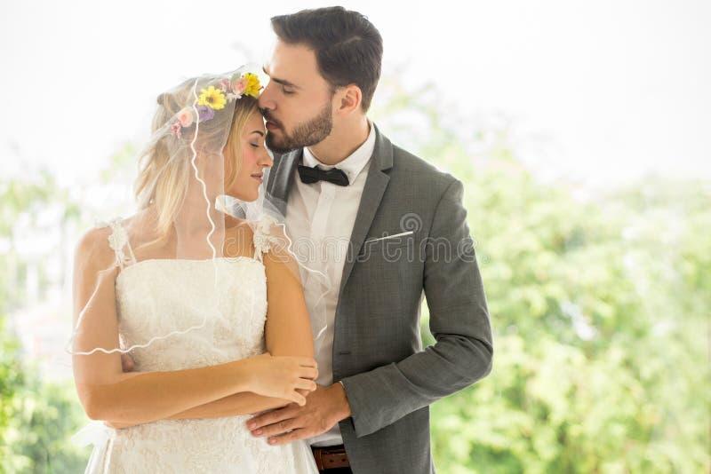 bruden och brudgummen för unga par som parkerar den förälskade gifta sig kysser i Nygifta personer Closeupstående av ett härligt  royaltyfri fotografi