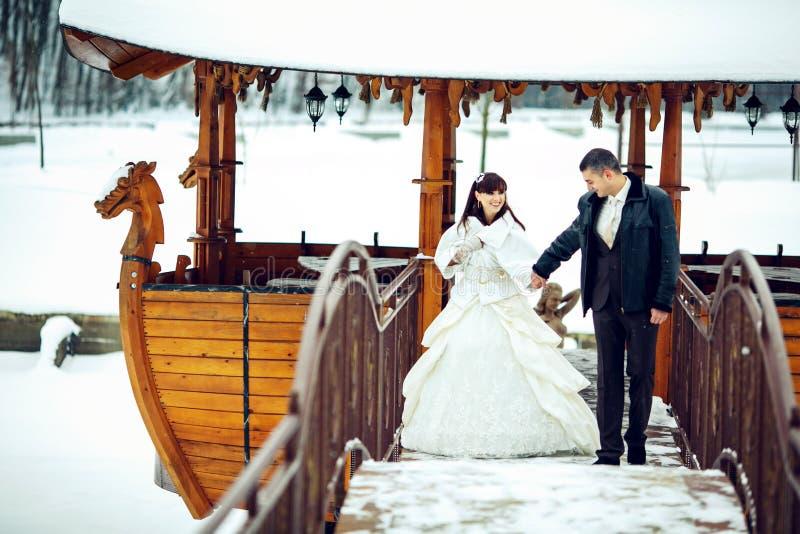 Bruden och brudgummen går på bron från ett stilfullt träfartyg in arkivfoto