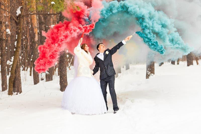 Bruden och brudgummen har gyckel på deras vinterbröllop royaltyfri fotografi