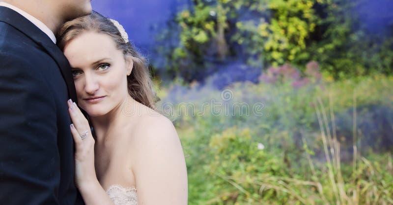 Bruden och brudgummen i skog med lilor röker royaltyfria foton