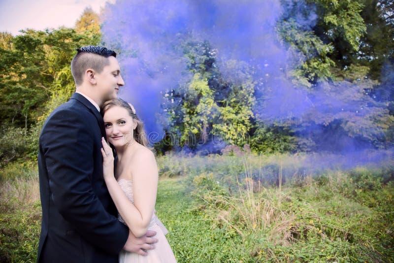 Bruden och brudgummen i skog med lilor röker fotografering för bildbyråer