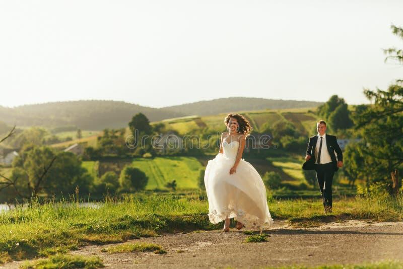 Bruden och brudgummen kör längs byvägen som tycker om sommarweath fotografering för bildbyråer
