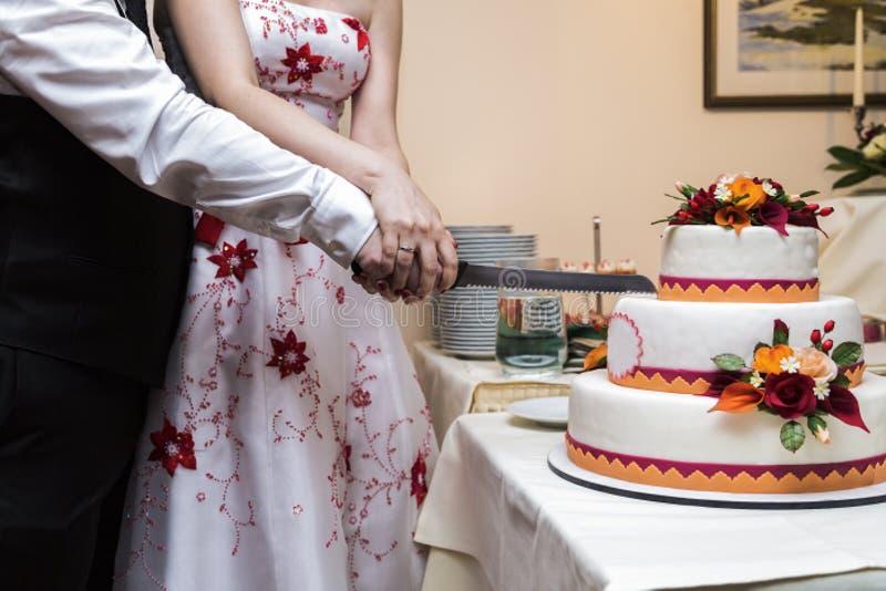 Bruden och brudgummen klipper med den vita stora härliga bröllopstårtan för kniven royaltyfri fotografi
